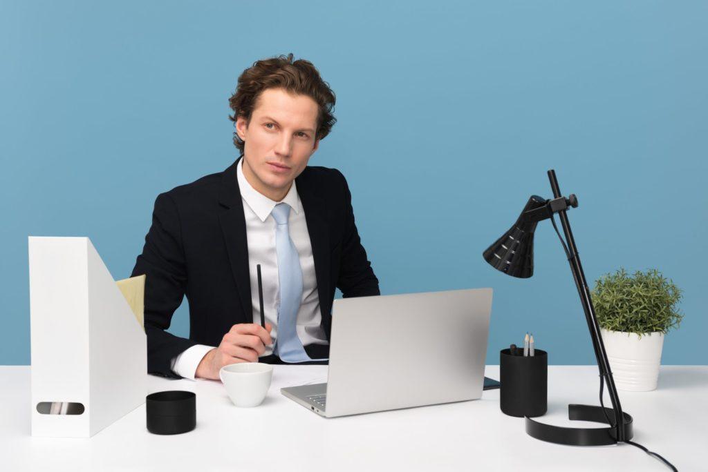 man in suit next to laptop