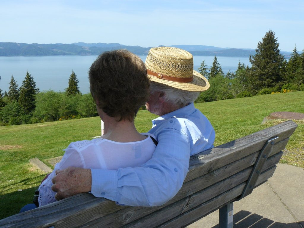 Image of couple sitting on a bench overlooking a lake