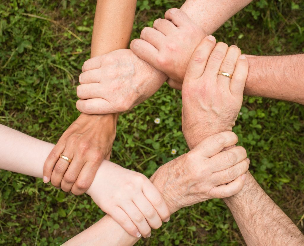 group of people holding eachother's wrists