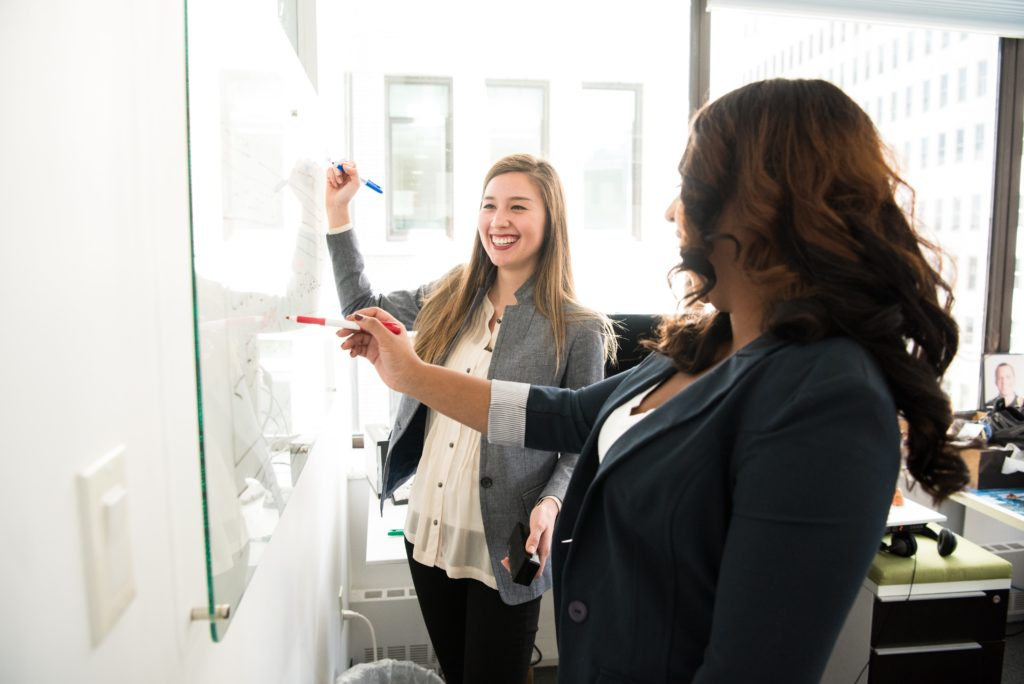 two women making a plan together on white board