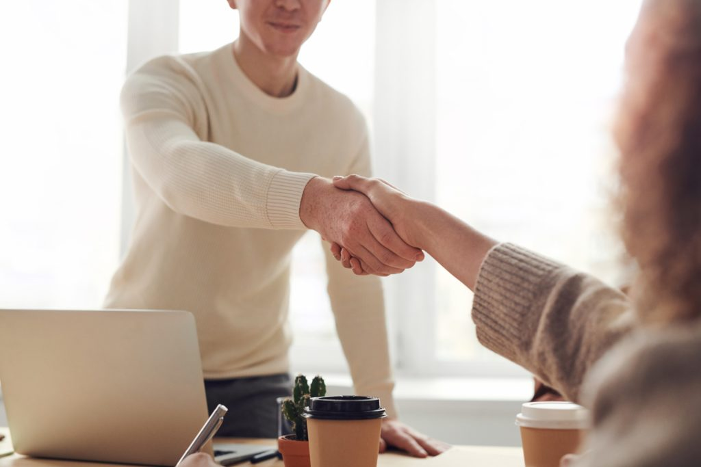 two people shaking hands and smiling